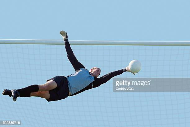 Goalkeeper attempting to prevent the ball entering the net