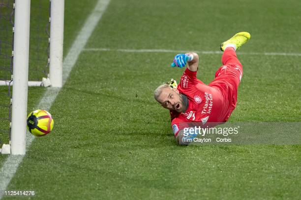 Goalkeeper Baptiste Reynet of Toulouse makes a fingertip save to push a penalty kick from Stephane Bahoken of Angers onto the post during the...