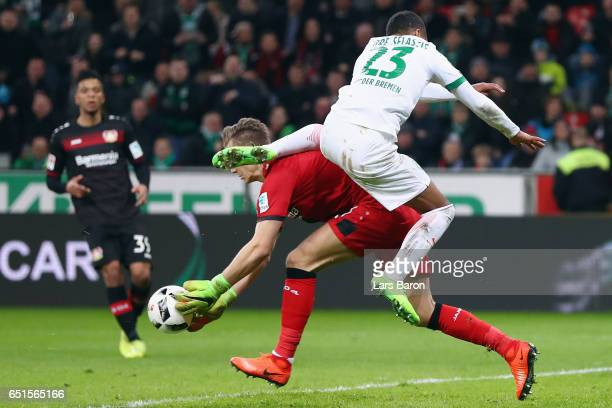 Goalkeeper Bernd Leno of Leverkusen is hit by Theodor Gebre Selassie of Bremen during the Bundesliga match between Bayer 04 Leverkusen and Werder...