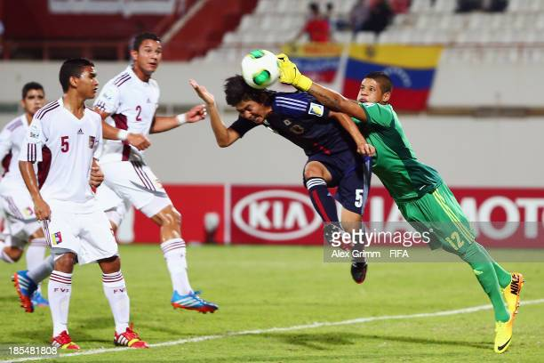 Goalkeeper Beycker Velasquez of Venezuela is challenged by Rikiya Motegi of Japan during the FIFA U-17 World Cup UAE 2013 Group D match between Japan...