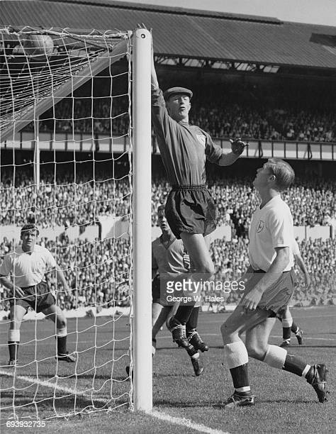 Goalkeeper Bill Brown of Spurs tips the ball over the crossbar as team mate and right back Peter Baker looks on during the Tottenham Hotspur vs...