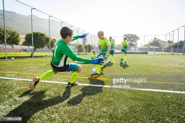 goalkeeper blocking soccer shots in training - tiro a portería fotografías e imágenes de stock