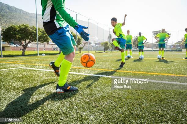 goalkeeper blocking soccer shots in training - shooting at goal stock-fotos und bilder