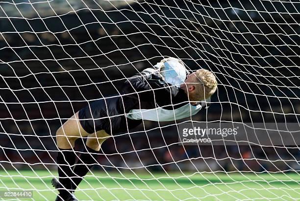 Goalkeeper blocking the ball at soccer match