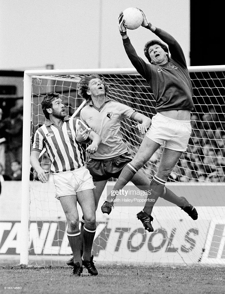 Goalkeeper Bob Bolder (R) of Sheffield Wednesday saves the ball alongside teammate Mike Pickering (L) and Ross Jenkins (C) of Watford during a Division Two match between Watford and Sheffield Wednesday at Vicarage Road in Watford on the 24th April, 1982.