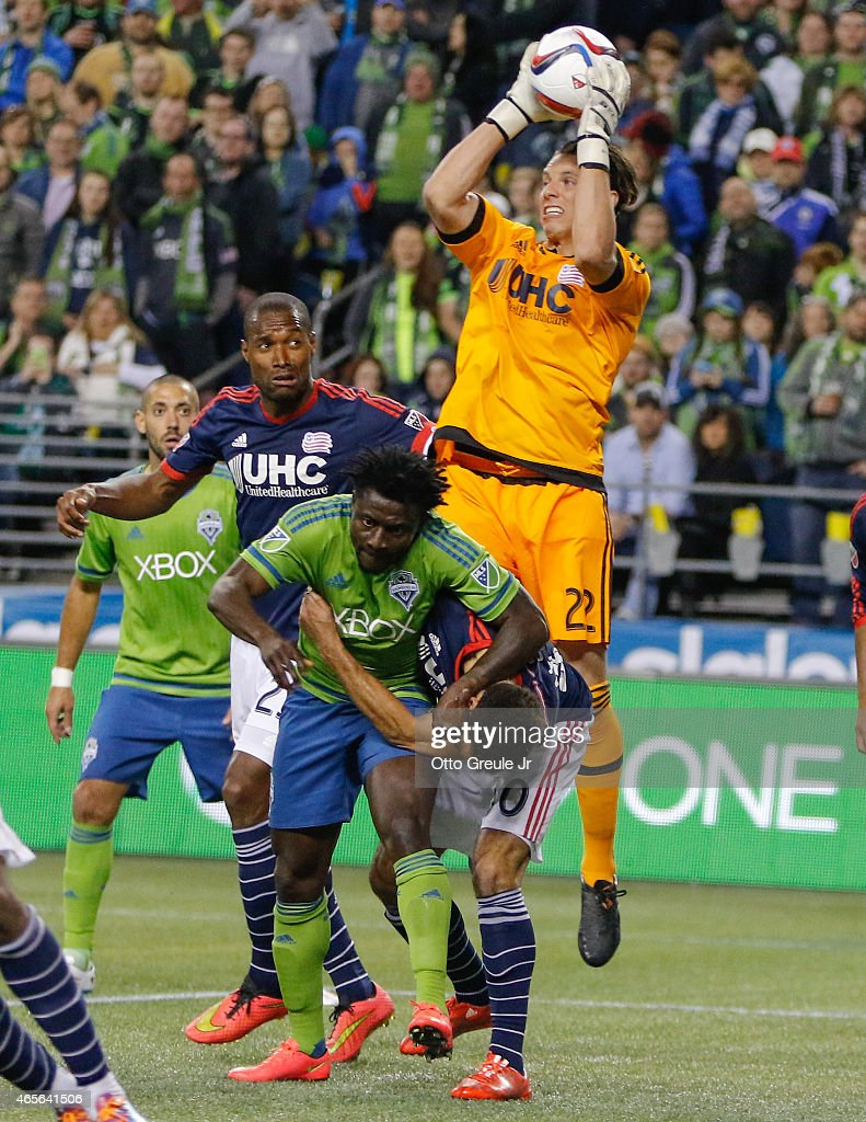 Goalkeeper Bobby Shuttleworth #22 of the New England Revolution blocks a shot as Obafemi Martins #9 of the Seattle Sounders FC battles Kevin Alston #30 at CenturyLink Field on March 8, 2015 in Seattle, Washington. The Sounders defeated the Revolution 3-0.