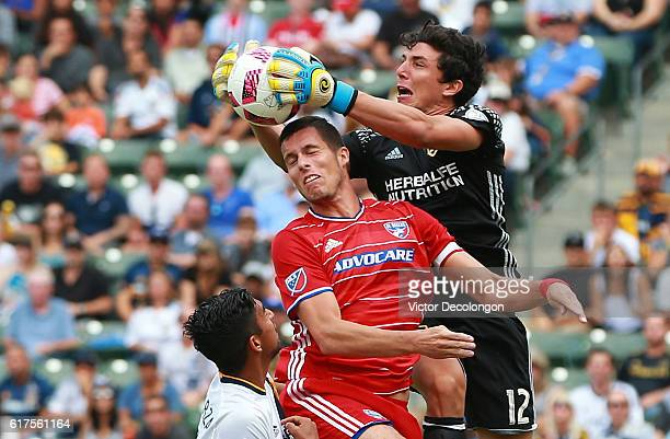 Goalkeeper Brian Rowe of the Los Angeles Galaxy makes a save as Matt Hedges of FC Dallas tries to get a head on the cross while A J DeLaGarza of the...