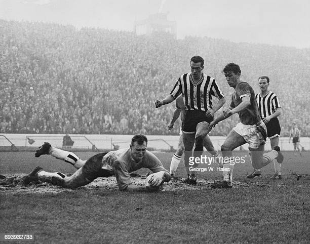 Goalkeeper Bryan Harvey of Newcastle United dives at the feet of Johnny Brooks inside forward for Chelsea as Bill Thompson the centre half for...