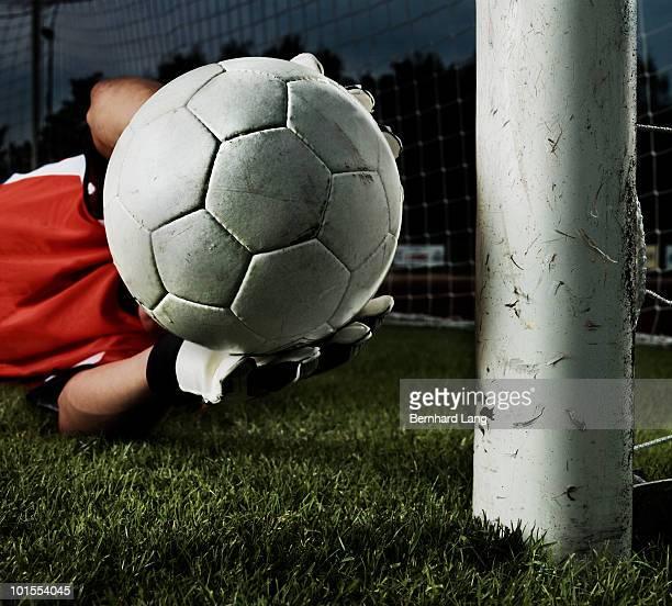 goalkeeper catching ball, close up - torhüter stock-fotos und bilder