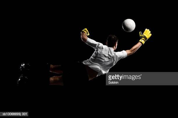 goalkeeper catching soccer ball, rear view - portero atleta fotografías e imágenes de stock
