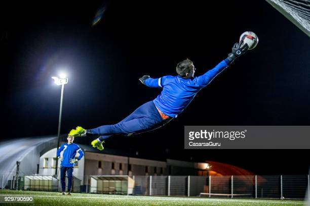 goalkeeper catching the ball in mid air - goalie goalkeeper football soccer keeper stock pictures, royalty-free photos & images