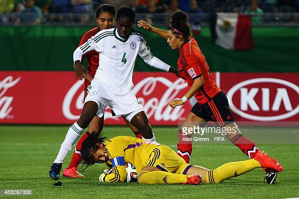 Goalkeeper Cecilia Santiago of Mexico is challenged by Asisat Oshoala of Nigeria during the FIFA U20 Women's World Cup Canada 2014 group C match...