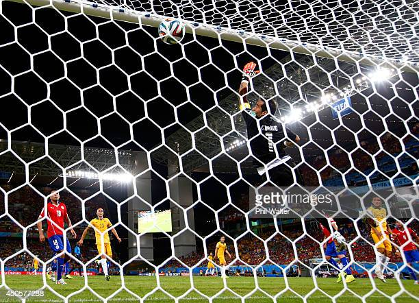 Goalkeeper Claudio Bravo of Chile fails to stop a header by Tim Cahill of Australia for his team's first goal during the 2014 FIFA World Cup Brazil...