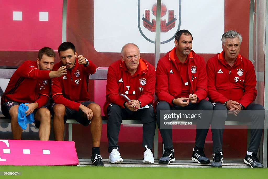 Goalkeeper coach Toni Tapalovic, assistant coach Davide Ancelotti, assistant coach Hermann Gerland, assistant coach Paul Clement and head coach Carlo Ancelotti of Bayern Muenchen sit on the bench during the friendly match between SV Lippstadt and FC Bayern at Stadion am Bruchbaum on July 16, 2016 in Lippstadt, Germany.