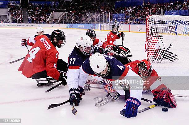 Goalkeeper Corbin Watson of Canada stretches for the puck under the pressure of Joshua Pauls and Brody Roybal of the United States during the Ice...