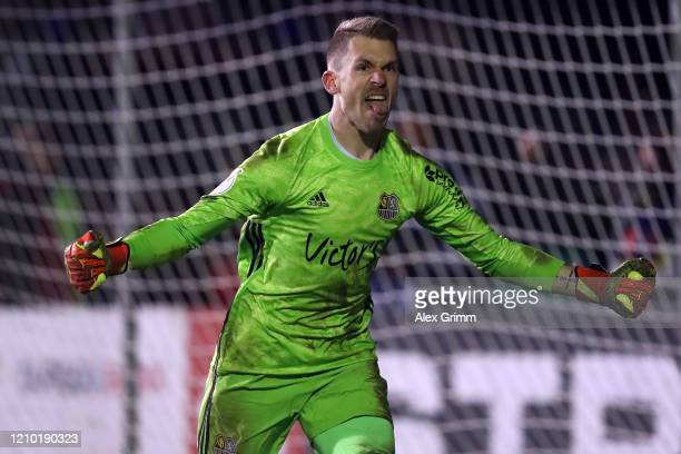 Goalkeeper Daniel Batz of Saarbruecken celebrates after saving a penalty from Mathias Zanka Jørgensen of Fortuna Dusseldorf to give his side victory...