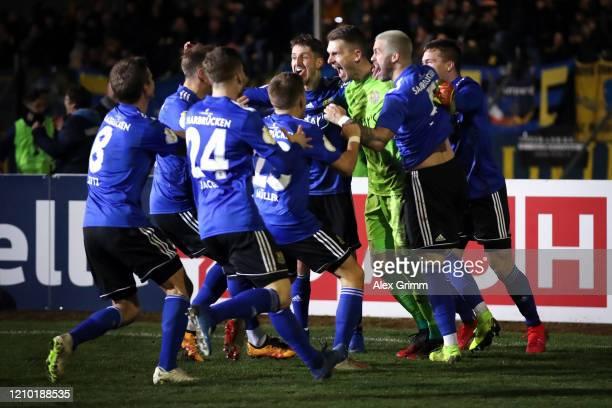 Goalkeeper Daniel Batz of Saarbruecken celebrates with team mates after saving a penalty from Mathias Zanka Jørgensen of Fortuna Dusseldorf to give...