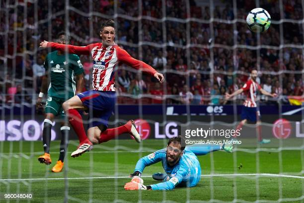Goalkeeper Daniel Gimenez of Real Betis Balompie stops the strike of Fernando Torres of Atletico de Madrid during the La Liga match between Club...
