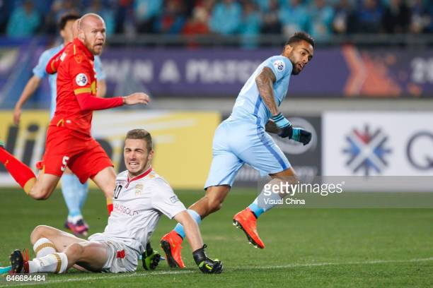 Goalkeeper Daniel Margush of Adelaide United falls on the ground as Alex Teixeira of Jiangsu Suning makes a shoot during the AFC Champions League...