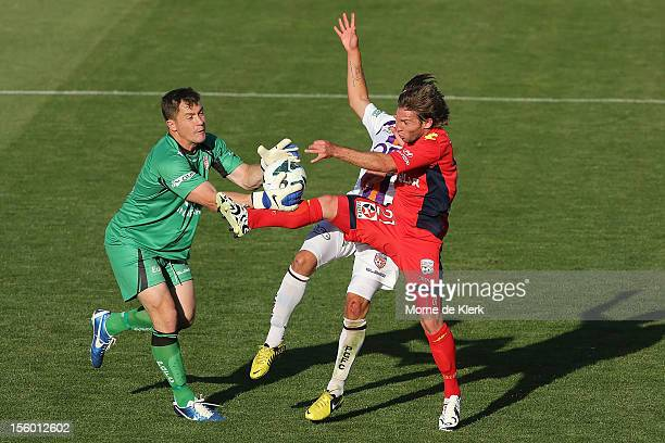 Goalkeeper Daniel Vukovic and defender Joshua Risdon of Perth clash with Jeronimo Neumann of Adelaide during the round six ALeague match between...