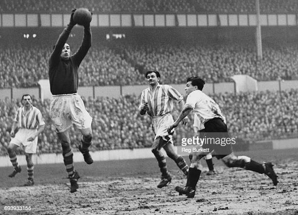 Goalkeeper Dennis Herod of Stoke City is challenged by centre forward Len Duquemin of Spurs as Stoke City centre back Frank Mountford C looks on...