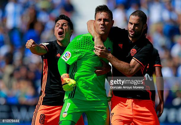 Goalkeeper Diego Alves of Valencia CF celebrates stopping a penalty shot with teammates Mario Suarez and Enzo Perez during the La Liga match between...