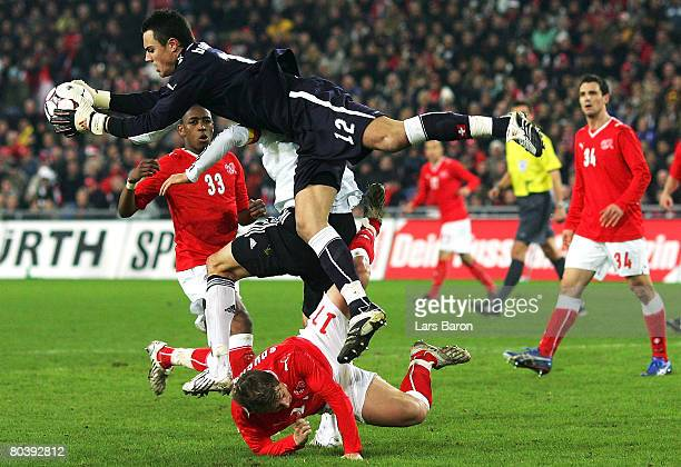 Goalkeeper Diego Benaglio of Switzerland in action with team mate Christoph Spycher and Michael Ballack of Germany during the international friendly...
