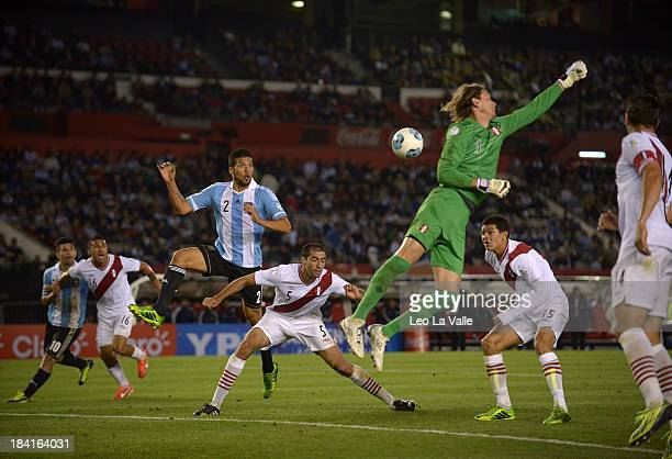 Goalkeeper Diego Penny Valdez of Peru misses a ball as Ezequiel Garay of Argentina jumps for a header during a match between Argentina and Peru as...