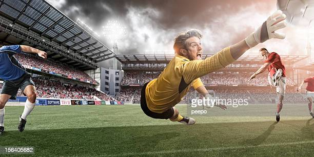 goalkeeper dives to make heroic save - goalie goalkeeper football soccer keeper stock pictures, royalty-free photos & images