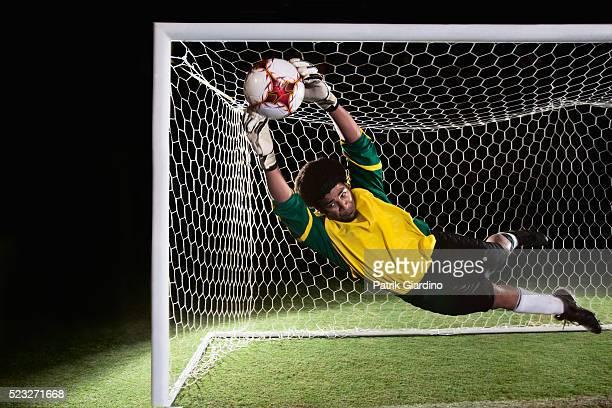 goalkeeper diving for ball - ゴールキーパー ストックフォトと画像