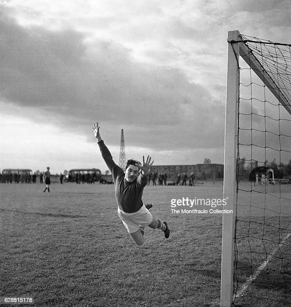 A goalkeeper diving through the air as he attempts to save a ball in a football game between Royal Airforce staff as a crowd watches on airbase...