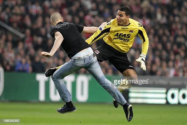 Goalkeeper Esteban Alvarado Brown of AZ Alkmaar retaliates as he is attacked by a supporter during the Dutch cup match between Ajax and AZ Alkmaar at...