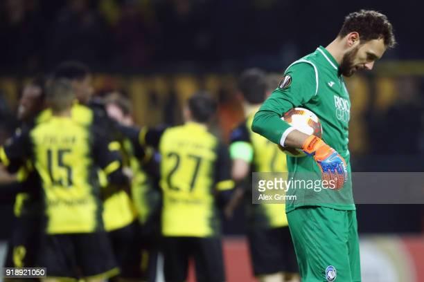 Goalkeeper Etrit Berisha of Bergamo reacts after Michy Batshuayi of Dortmund celebrates his team's third goal during UEFA Europa League Round of 32...