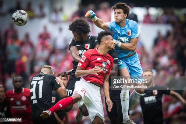 Goalkeeper Fabian Giefer of Augsburg clears the ball ahead of team mate Caiuby and Karim Onisiwo of Mainz during the Bundesliga match between 1. FSV...