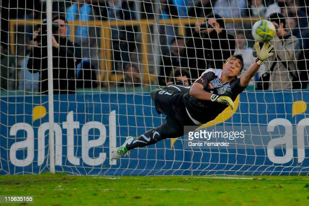 Goalkeeper Fernando Muslera tries to stop a penalty during the shoot out during a friendly match between Uruguay and Holland at Centenario Stadium on...