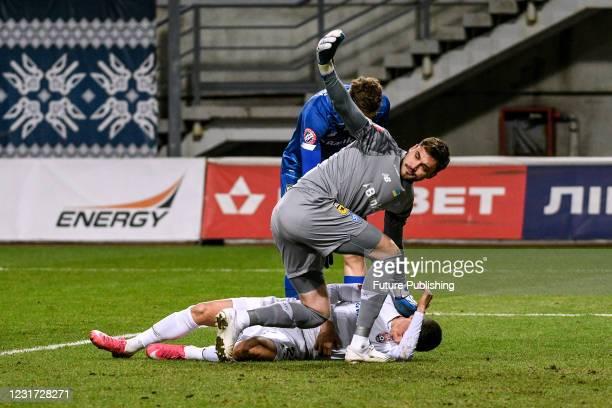 Goalkeeper Georgiy Bushchan of FC Dynamo Kyiv stays by injured midfielder Dmytro Ivanisenia of FC Zorya Luhansk during the 2020/2021 Ukrainian...