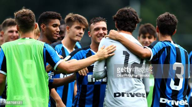 Goalkeeper Giacomo Pozzer of Inter is congratulated by team mates Lorenzo Colombini Chrystopher Attys Etienne Ludovic Youte Kinkoue and Elvis Rikard...