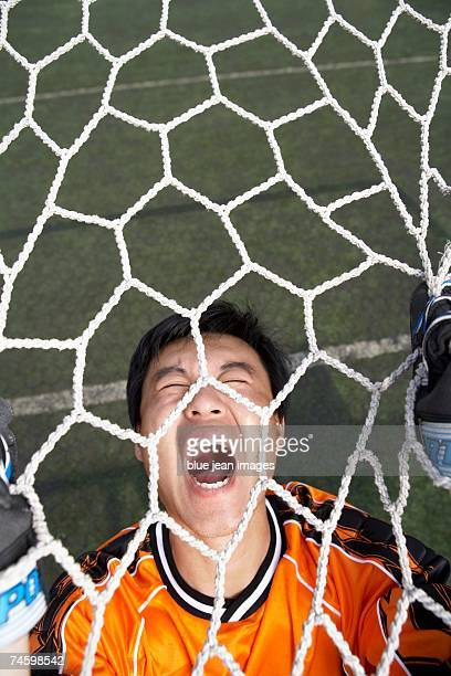 goalkeeper grasps the net and screams in defeat - uvula stock photos and pictures