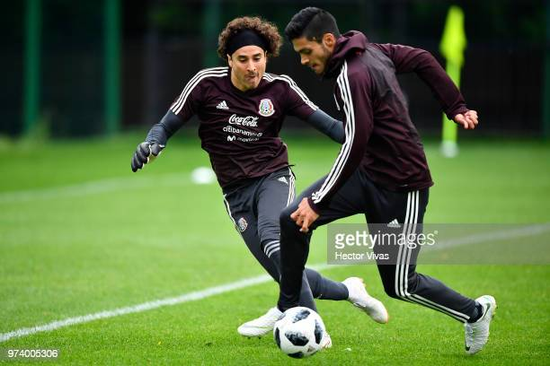 Goalkeeper Guillermo Ochoa and Raul Jimenez of Mexico struggle for the ball during a training session at FC Strogino Stadium on June 12 2018 in...