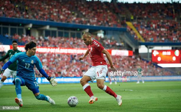 Goalkeeper Guillermo Ochoa of Mexico and Martin Braithwaite of Denmark compete for the ball during the international friendly match between Denmark...