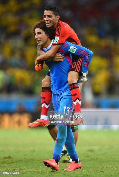 Goalkeeper Guillermo Ochoa of Mexico celebrates with Javier Aquino after their 00 draw with Brazil during the 2014 FIFA World Cup Brazil Group A...