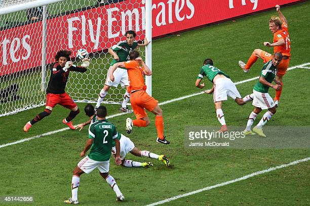 Goalkeeper Guillermo Ochoa of Mexico makes a save after a shot at goal by Stefan de Vrij of the Netherlands during the 2014 FIFA World Cup Brazil...