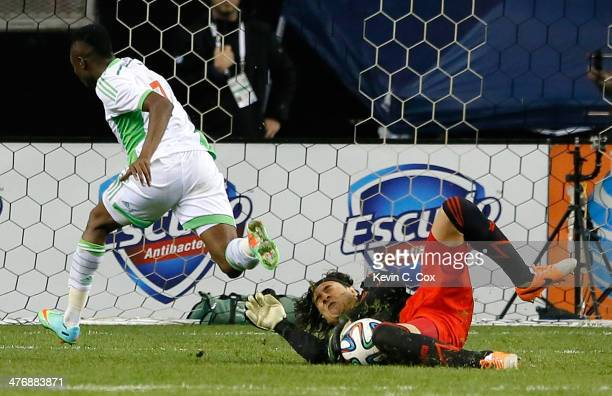 Goalkeeper Guillermo Ochoa of Mexico saves a shot on goal by Ahmed Musa of Nigeria at Georgia Dome on March 5 2014 in Atlanta Georgia