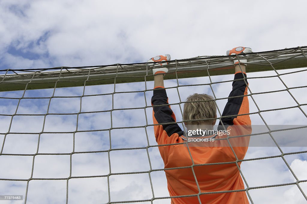 Goalkeeper hanging on goal : Photo