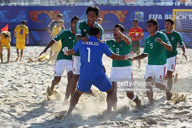Goalkeeper, Hector Robles of Mexico is congratulated by team mates after his penalty winning save during the FIFA Beach Soccer World Cup Group D...