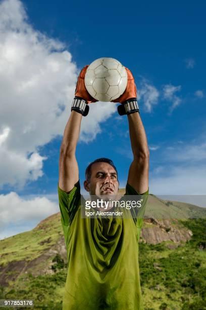 ゴールキーパーの上にサッカー ボールを保持