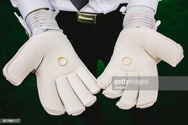 Goalkeeper holding wedding rings in gloves