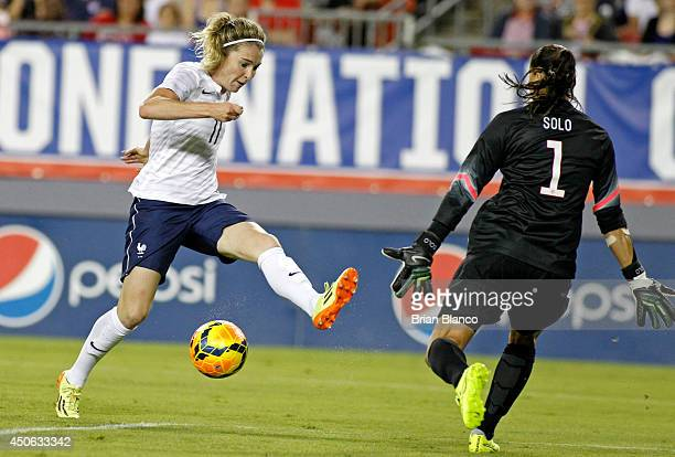 Goalkeeper Hope Solo of the United States defends against a shot by forward Laetitia Tonazzi of France during the second half of a women's friendly...