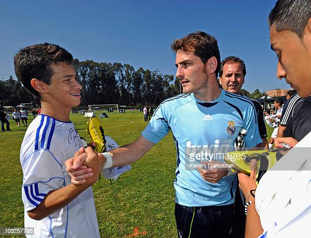 Goalkeeper Iker Casillas of Real Madrid greets a local youth soccer player participating in the Adidas training August 5 2010 in Westwood section of...