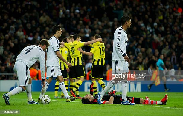 Goalkeeper Iker Casillas of Real Madrid lays defeated on the pitch while Mario Gotze of Borussia Dortmund celebrates with his teammates in the...